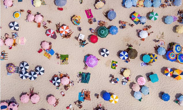 Can you find the cocktail umbrella hidden among the beach parasols?