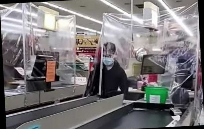 Grocery store cashiers work inside plastic tents for safety amid coronavirus